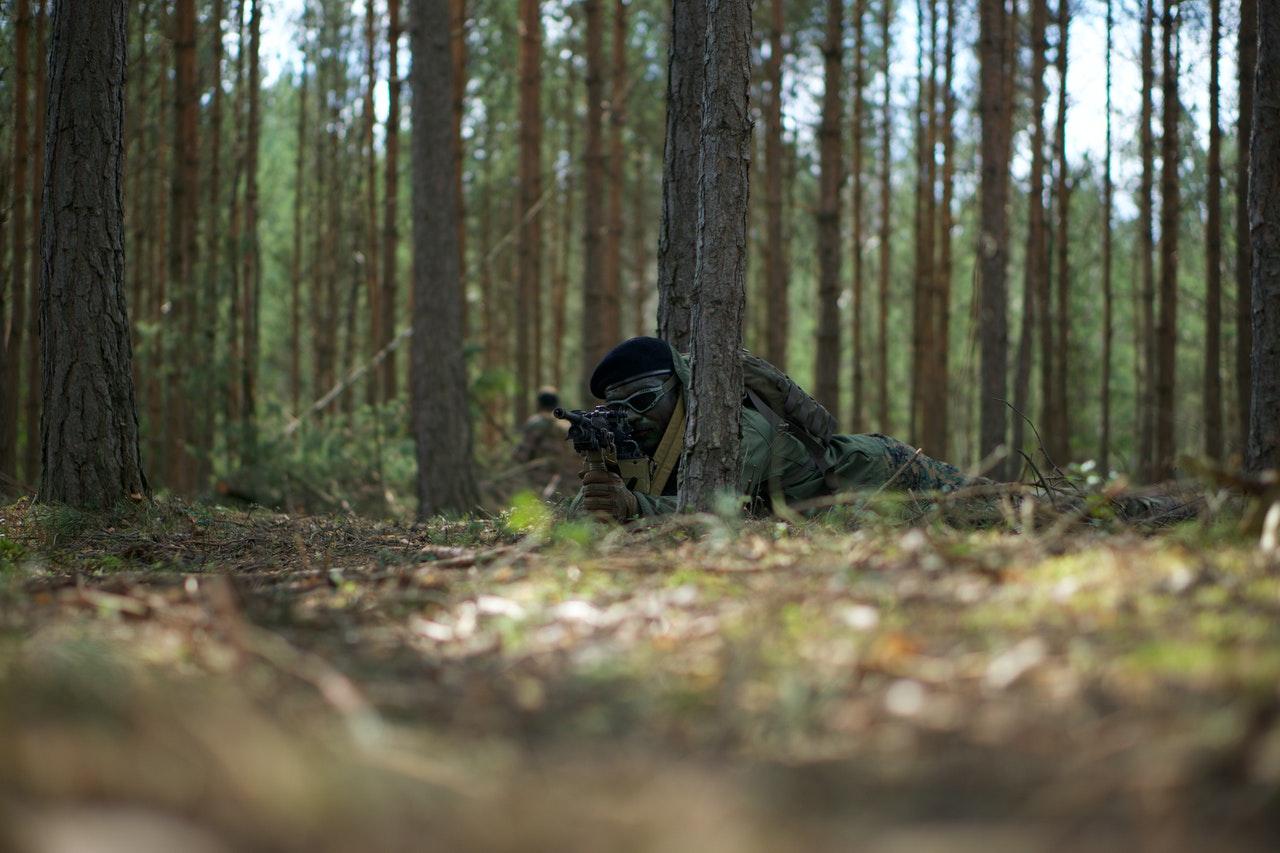 joueur d'airsoft allongé dans les bois