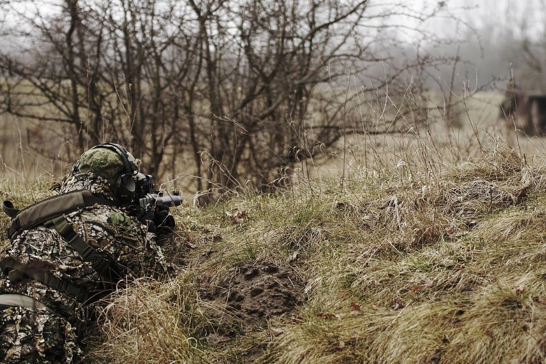 joueur d'airsoft au sniper allongé dans l'herbe
